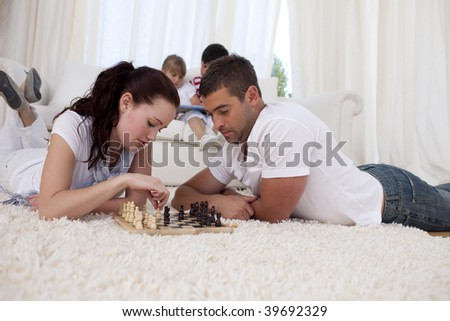 Couple playing chess on floor in living-room with their children on sofa - stock photo