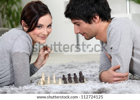 Couple playing chess whilst lying on the carpet