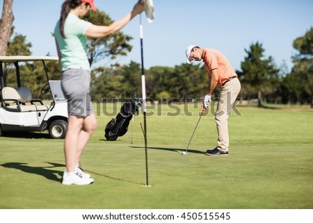 Couple playing golf together on golf course