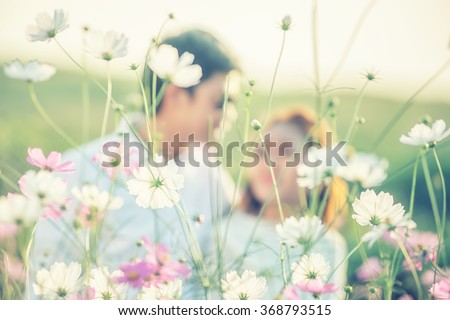 Couple playing in the garden flowers. Both happy and smiling on Valentine's Day, flower focus - stock photo