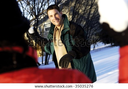 couple playing in the snow - stock photo
