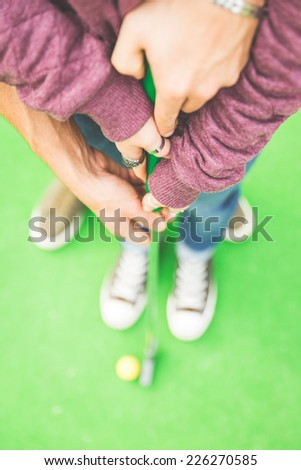 couple playing mini golf. Man helping his girlfriend to hold the club. concept of union and love - stock photo