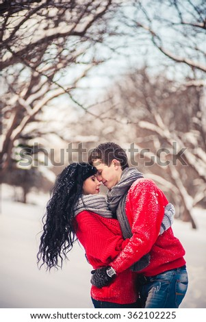 couple playing snowballs in the forest on a sunny day - stock photo
