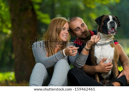 Couple Playing With Dog - stock photo