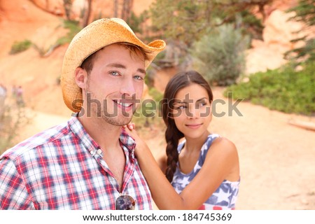 Couple portrait in american countryside outdoors. Smiling multiracial young couple in western USA nature. Man wearing cowboy hat and woman wearing USA flag shirt. - stock photo