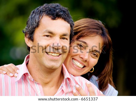 couple portrait outdoors smiling with a green background - stock photo