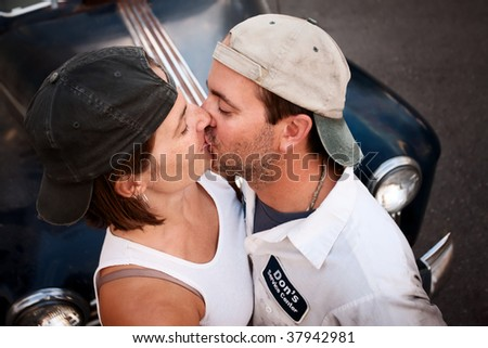 Couple posing with vintage sedan and kissing - stock photo