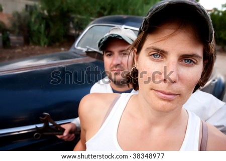 Couple posing with vintage sedan and tools - stock photo