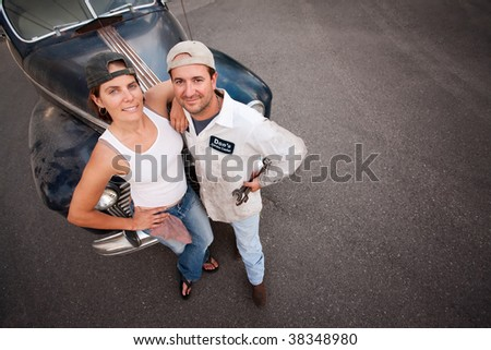 Couple posing with vintage sedan and tools