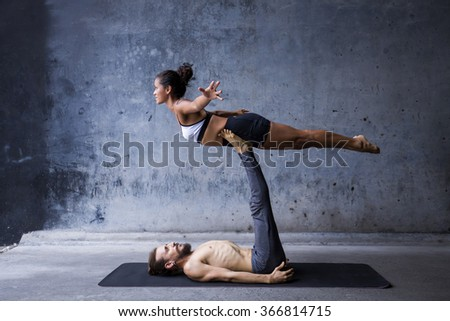 Couple practicing yoga together - stock photo