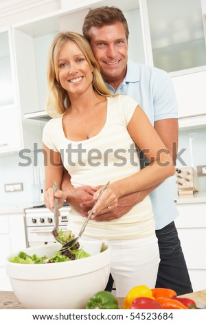 Couple Preparing Salad In Modern Kitchen