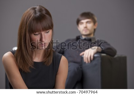 couple problem - sad woman sitting in foreground, man in background - stock photo