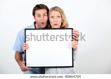 Couple pulling a funny face and holding a blank board ready for your text - stock photo