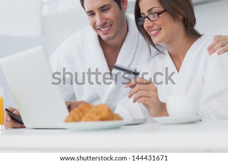 Couple purchasing online while having breakfast - stock photo