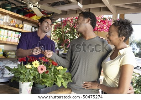 Couple purchasing plants in shop - stock photo