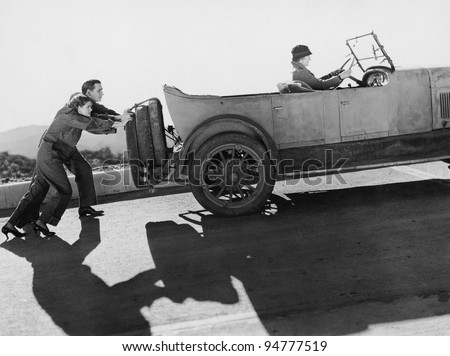 Couple pushing woman in car up hill - stock photo