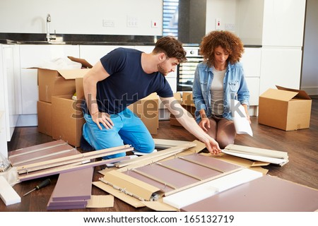 Couple Putting Together Self Assembly Furniture In New Home - stock photo