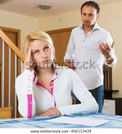 Couple quarrel. Upset ordinary man against unhappy blonde woman  at home - stock photo