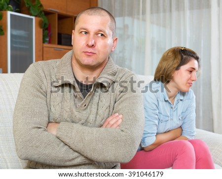 Couple quarrel. Upset ordinary man against unhappy woman in living room at home