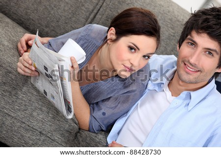 Couple reading a newspaper at home - stock photo