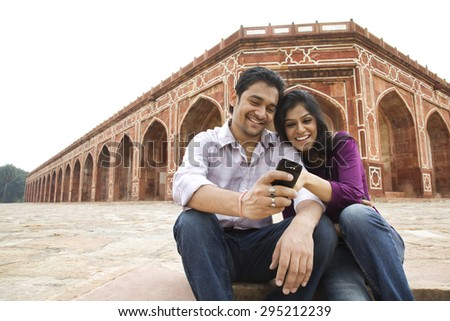 Couple reading an sms at Humayuns Tomb