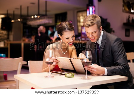Couple reading  at menu together in a restaurant - stock photo
