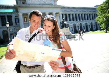 Couple reading city map in front of Prado museum, Madrid - stock photo