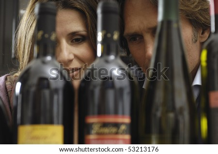 couple reading labels of bottles - stock photo