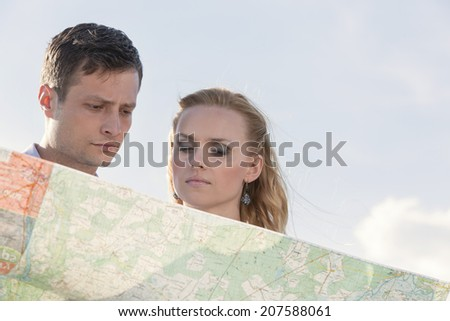 Couple reading map against sky - stock photo
