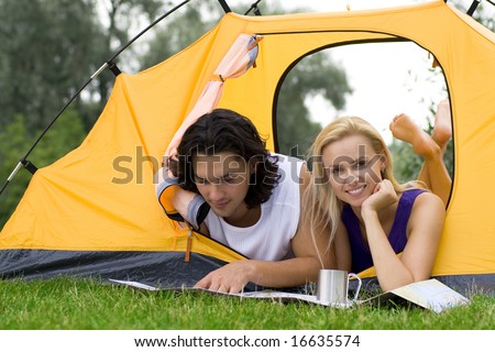 Couple Reading Map in Tent - stock photo
