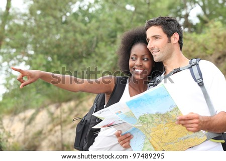 Couple reading map outdoors - stock photo