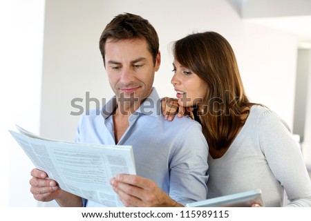 Couple reading news on newspaper and internet - stock photo