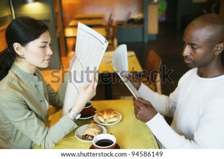 Couple reading newspaper in restaurant - stock photo
