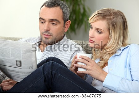 Couple reading newspaper on couch - stock photo