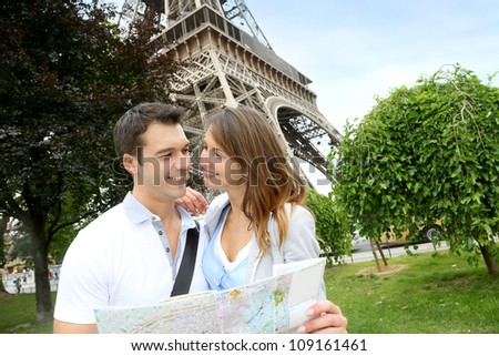 Couple reading tourist map in front of the Eiffel tower