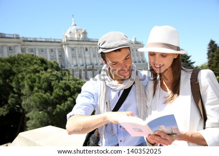 Couple reading traveler book by the Royal Palace of Madrid - stock photo