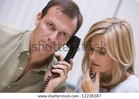 Couple receiving bad news over the phone at home - stock photo