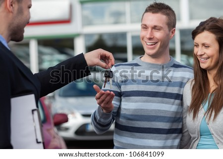 Couple receiving car keys by a dealer in a dealership - stock photo