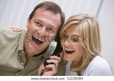 Couple receiving good news over the phone at home - stock photo