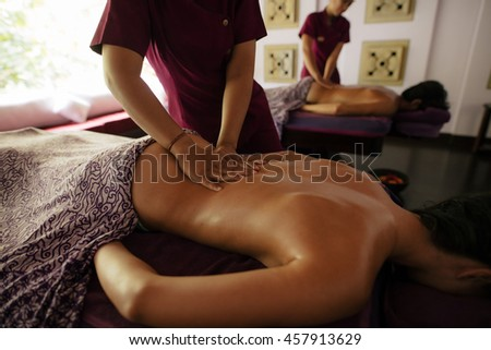 Couple receiving massage at day spa. Man and woman lying on massage table with female massage therapist. - stock photo