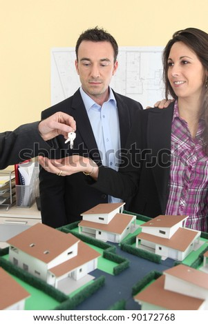 Couple receiving the keys to a new home - stock photo