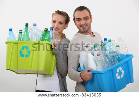 Couple recycling empty plastic bottles - stock photo