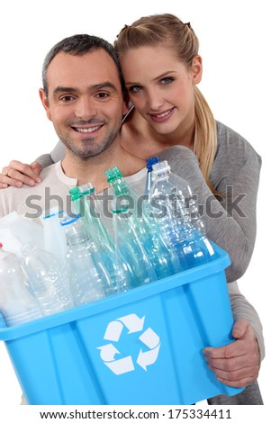 Couple recycling plastic bottles - stock photo
