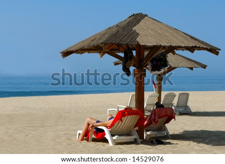 Couple Relaxes on Remote Beach - stock photo