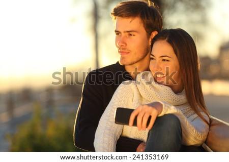 Couple relaxing and hugging looking at sunset sitting on a bench and holding a smart phone - stock photo