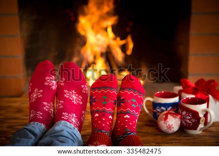 Couple relaxing at home. Feet in Christmas socks near fireplace. Winter holiday concept - stock photo