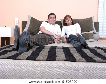 Couple relaxing at home on their bed - stock photo