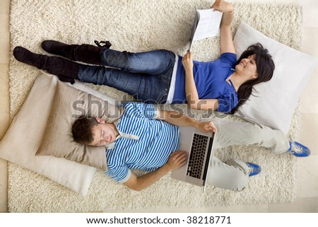Couple relaxing at home with a laptop and reading - stock photo