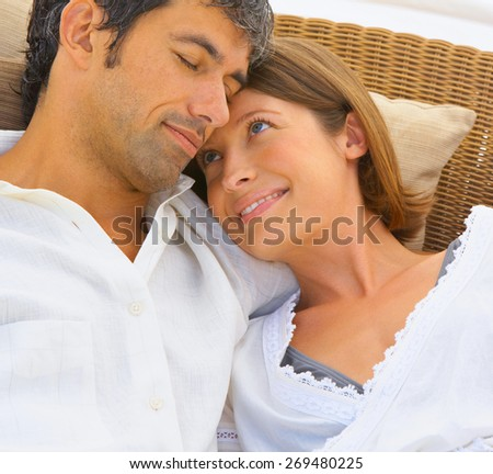 Couple relaxing by luxury hotel swimming-pool - stock photo