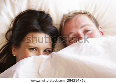 Couple Relaxing In Bed Hiding Under Bedclothes - stock photo